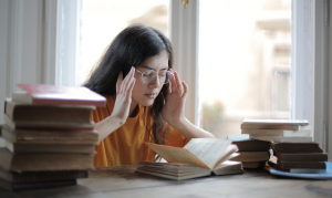 student touching her head with books on the table